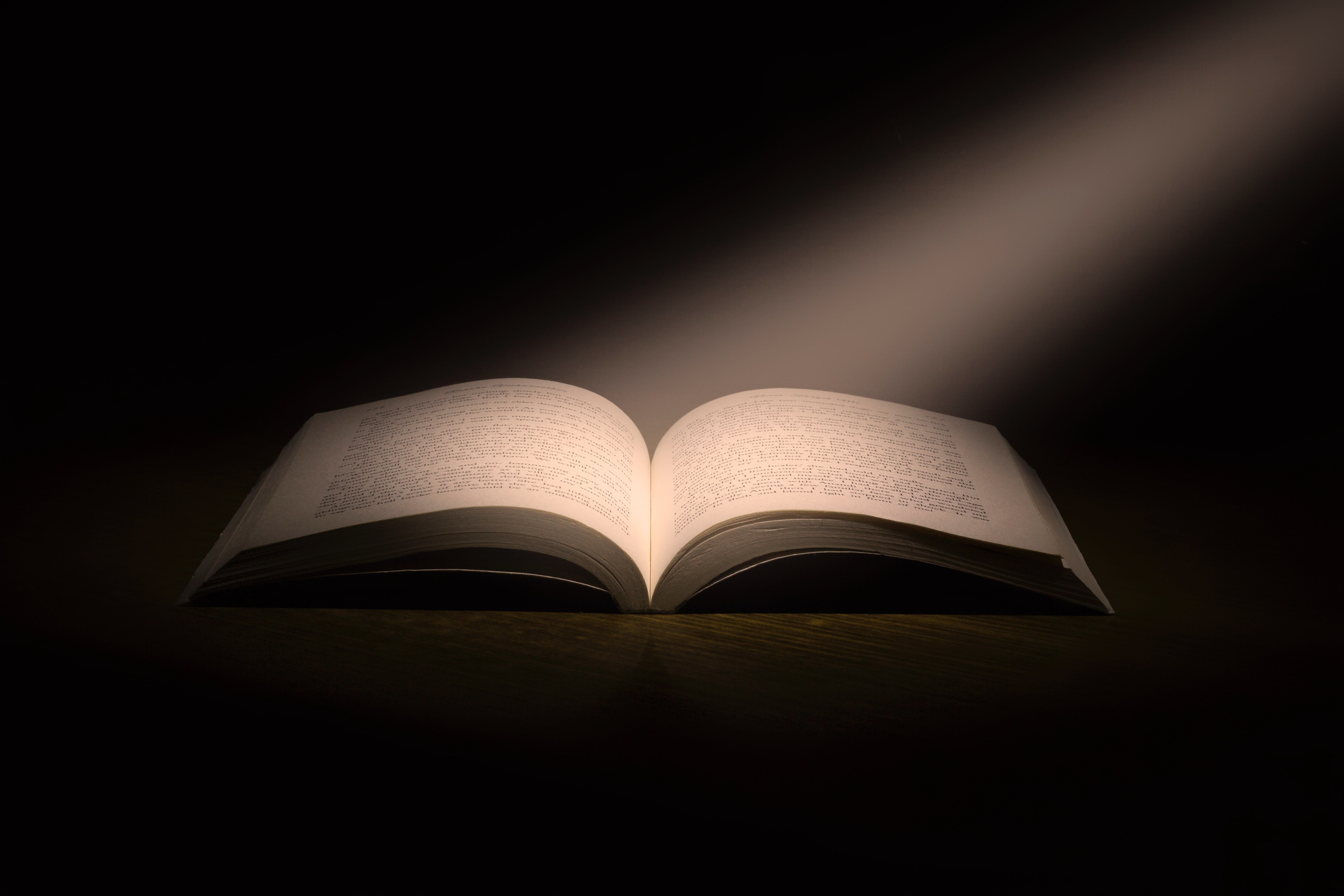 Buch im schwarzen Raum mit Lichtstrahl